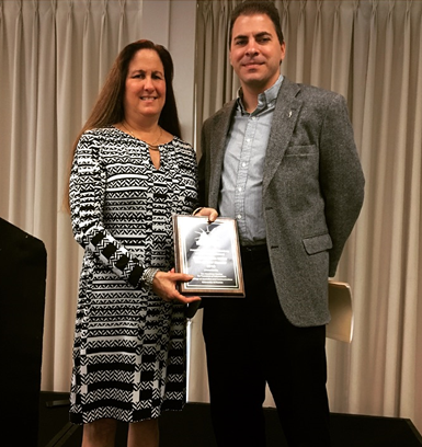Carol Marbin Miller and Executive Associate Dean Spiro Kiousis. Marbin Miller also accepted the award on behalf of her colleague on the project Audra D.S. Burch.